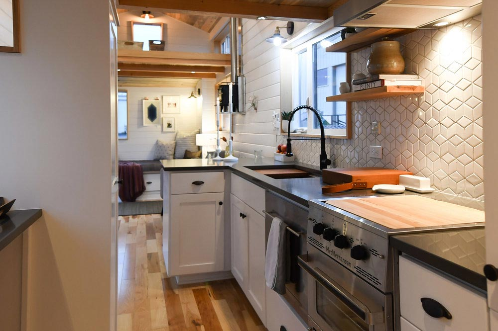 The kitchen has an L-shaped counter with a gray quartz top and white cabinets as a base