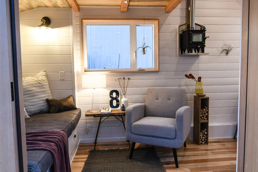 The living area also has a mini wood stove on one of the walls