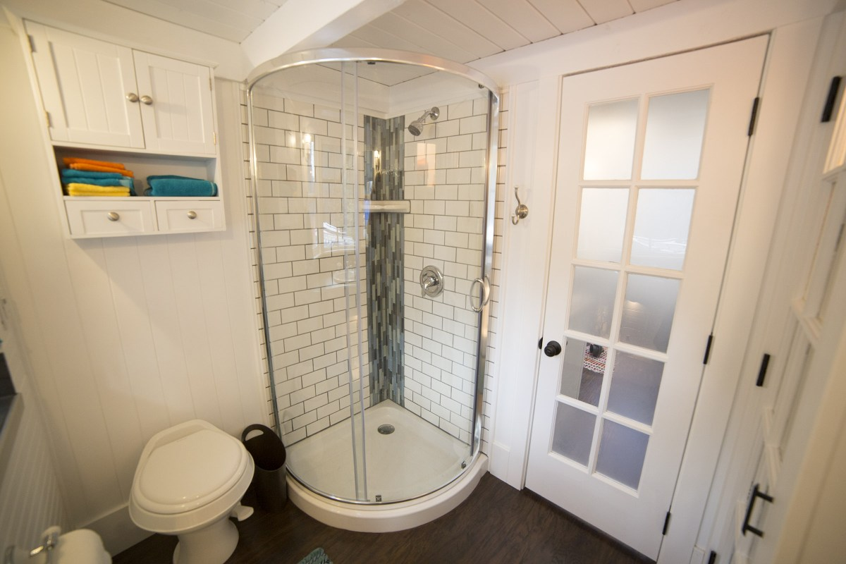 There's a curved shower in the corner, with a toilet and wall-mounted cabinet next to it
