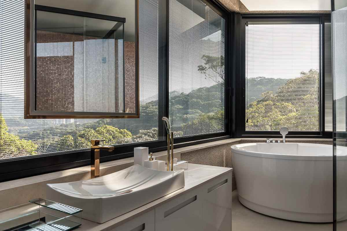 In this bathroom, a deep soaking tub takes the corners area, with large windows framing it