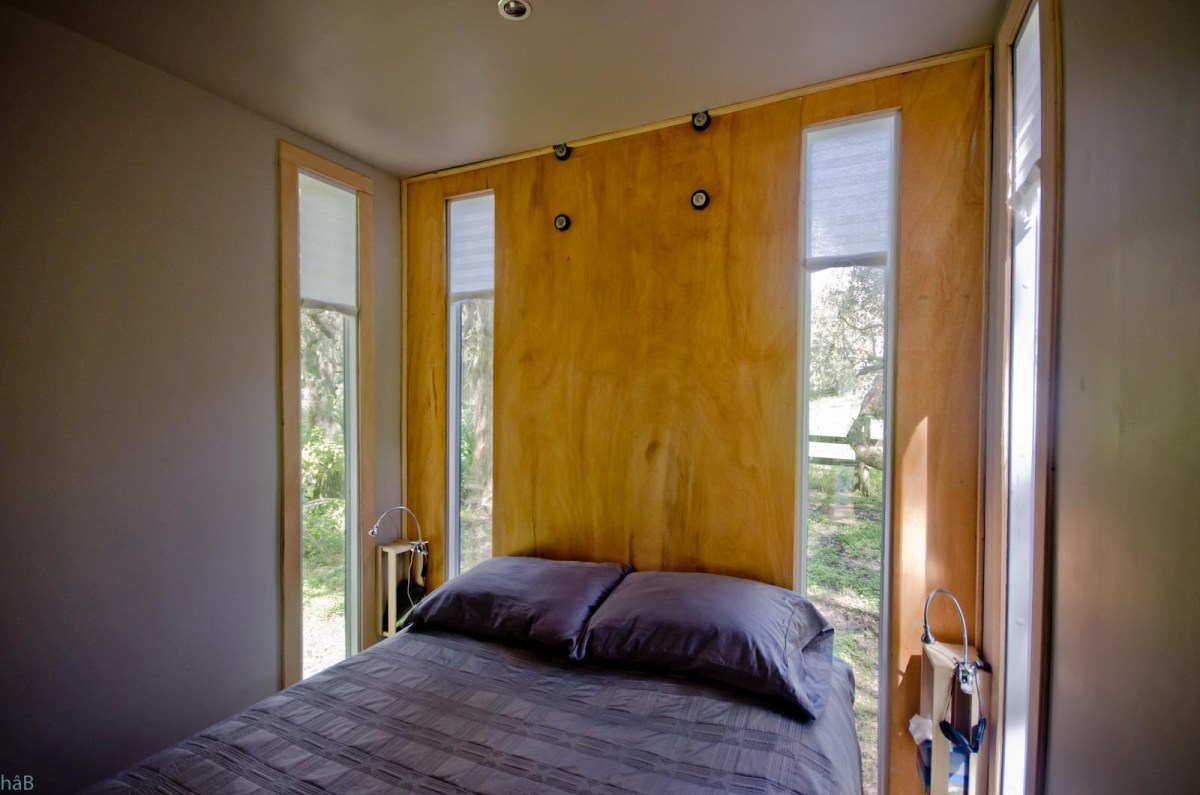 The bedroom has tall and slender windows in the corners