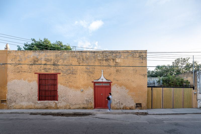 The red front door and window shutters offer a hint that this old building is actually in use