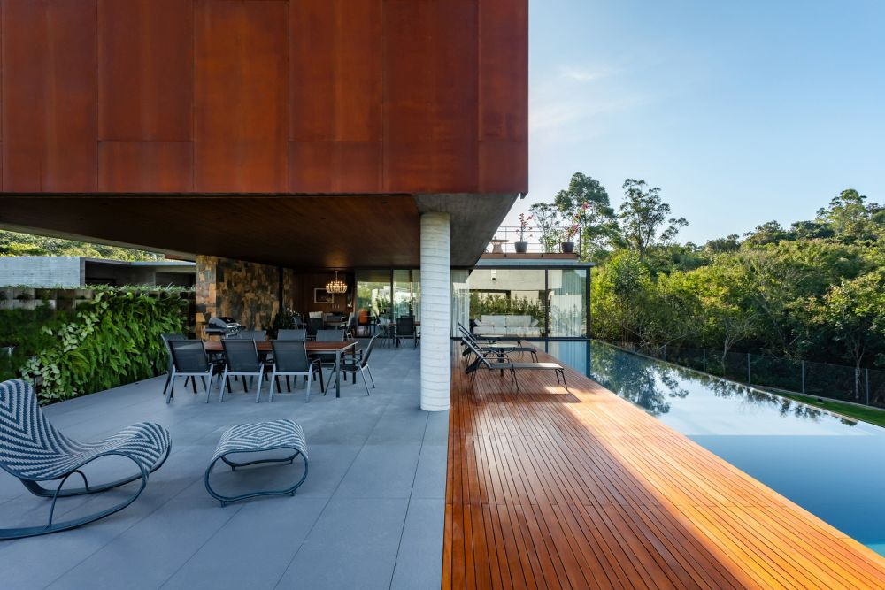 The Corten steel and exposed concrete are balanced out by the warmth of the wood and all the fresh and vibrant greenery