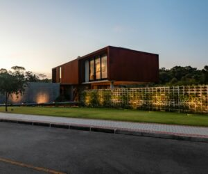 A Corten Steel And Concrete House Framed By The Most Beautiful Green Fence