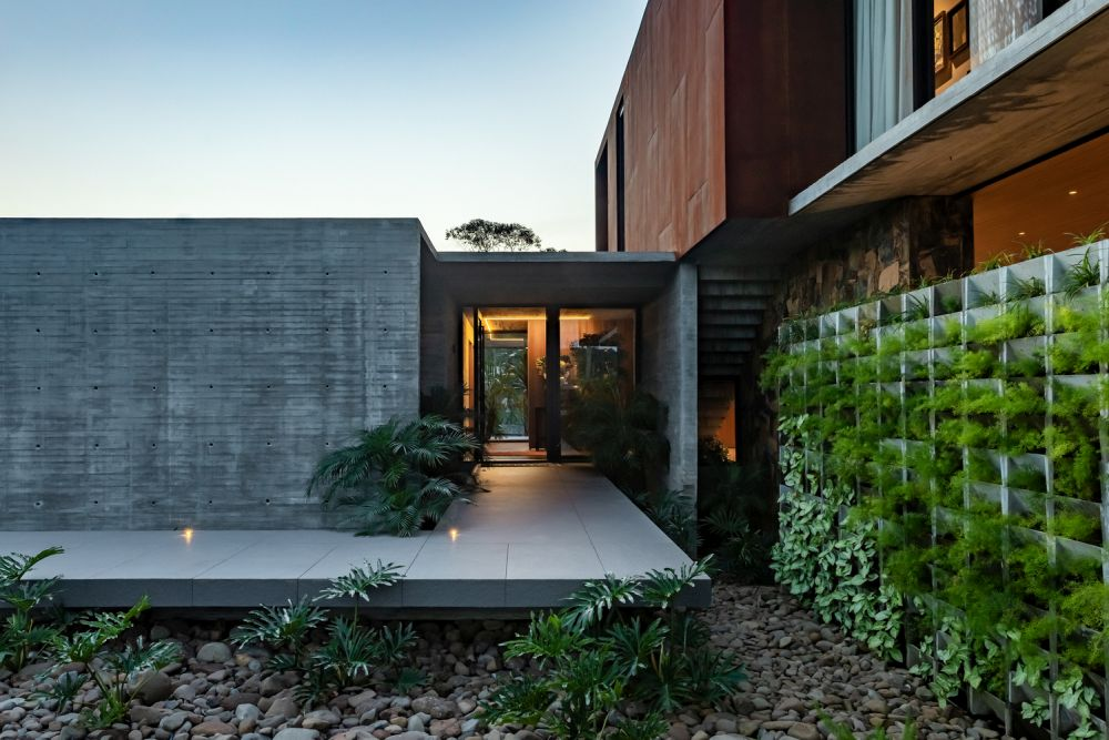 The entrance is nicely sheltered and framed by exposed concrete and lots of greenery