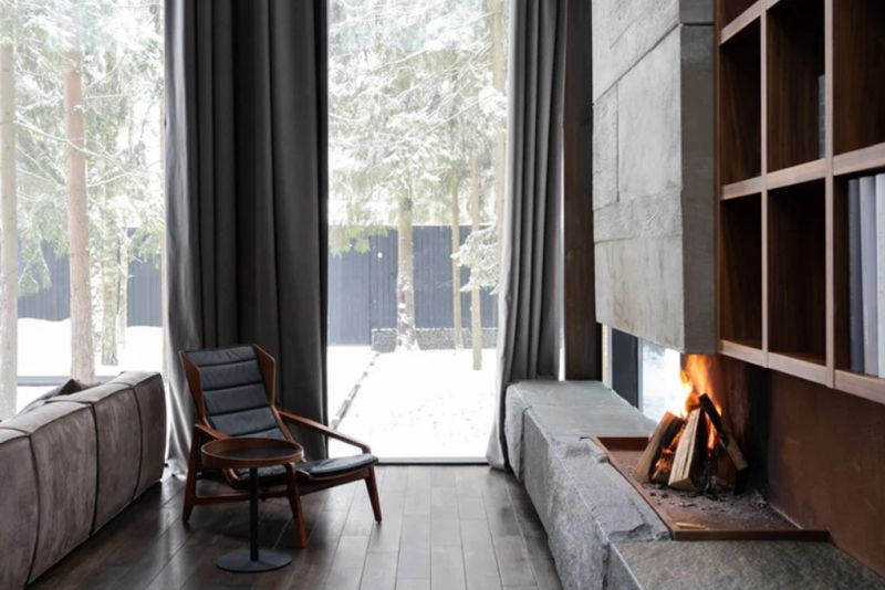 Exposed concrete and stone are used as accent materials in combination with natural wood