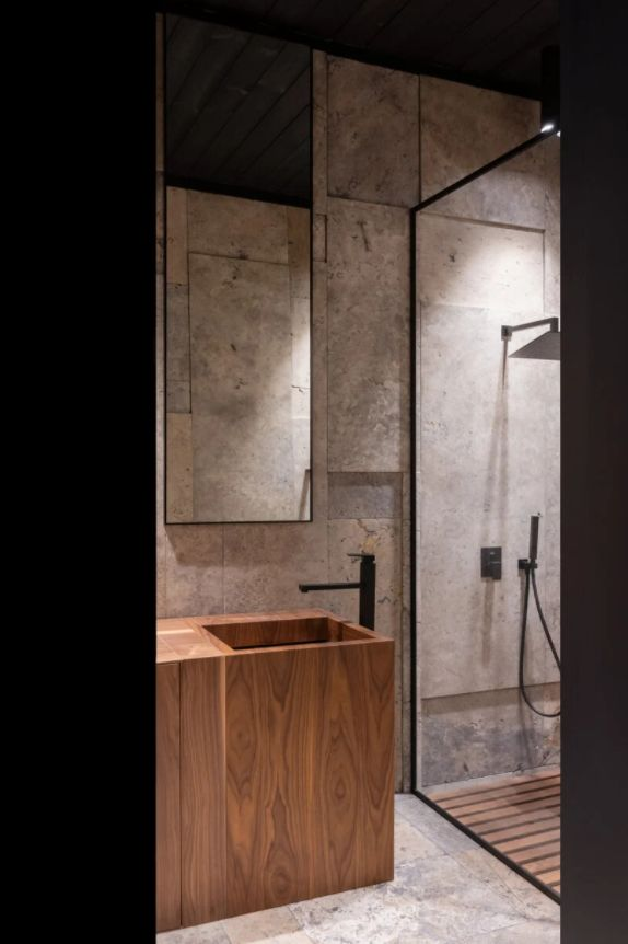 The bathroom features an elegant wooden sink/ vanity and a walk-in shower