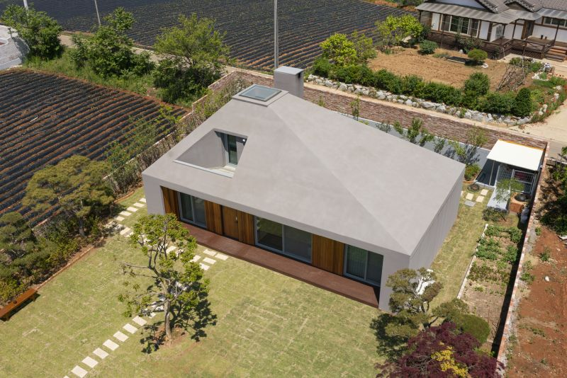 The roof is asymmetrical and flush with the walls, giving the house a tent-like look