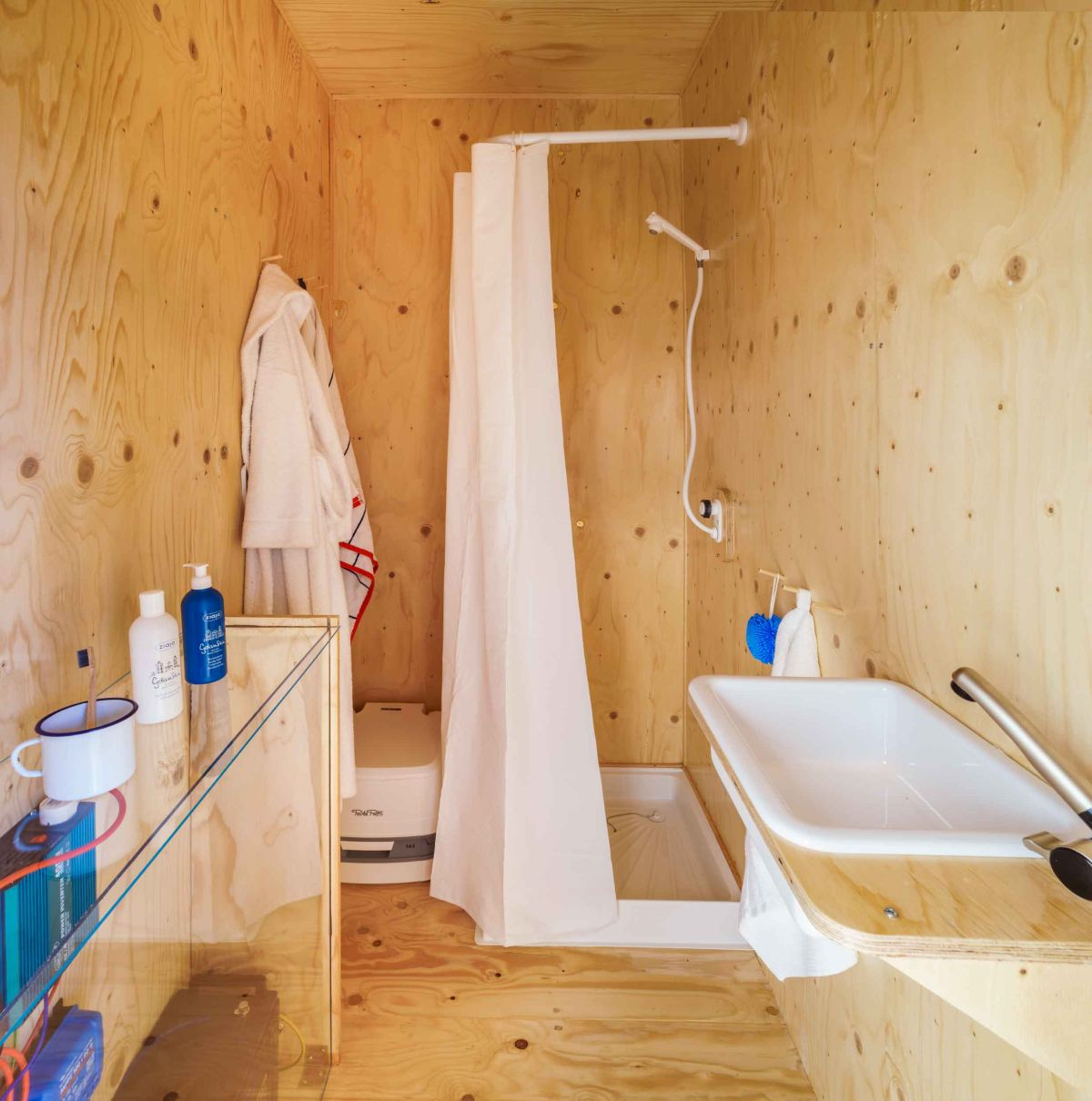The bathroom is small but manages to include a shower, toilet, sink and a storage unit