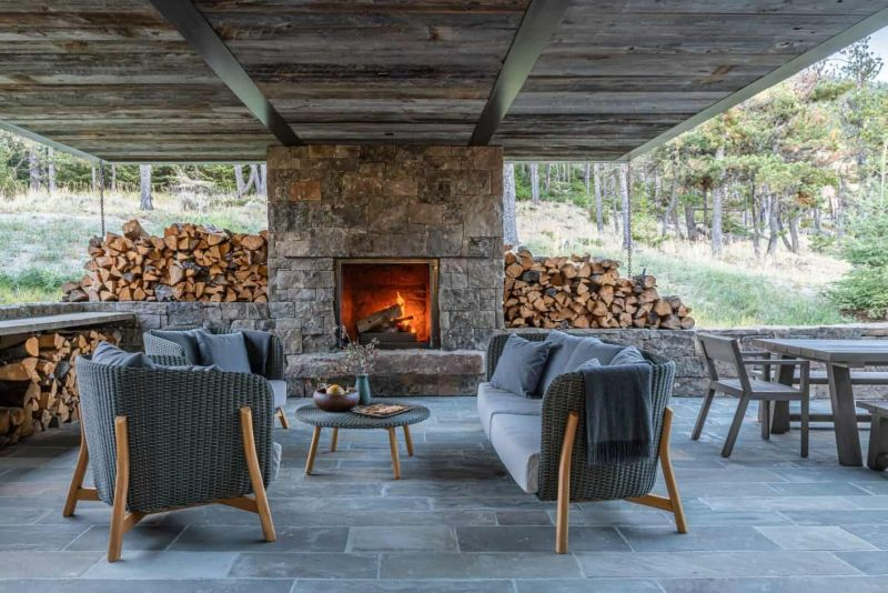 The patio is fitted with a large stone-clad fireplace