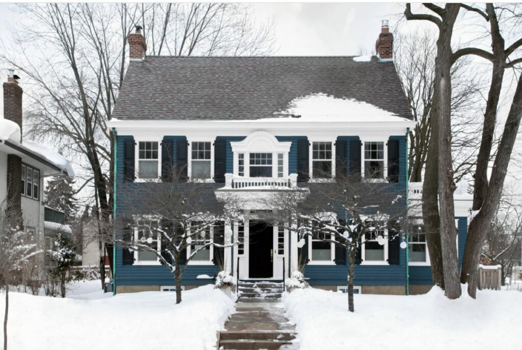 classic blue house in snow