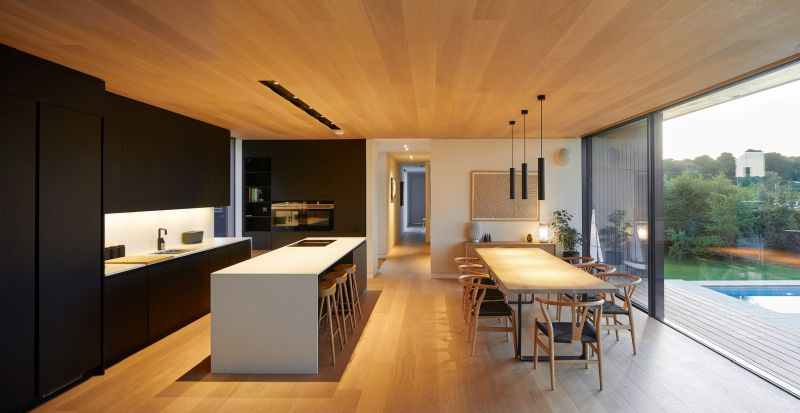 The open kitchen features black minimalist cabinetry and a white island