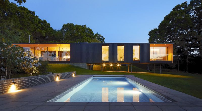 The swimming pool is built into the ground, lower than the floor level of the house