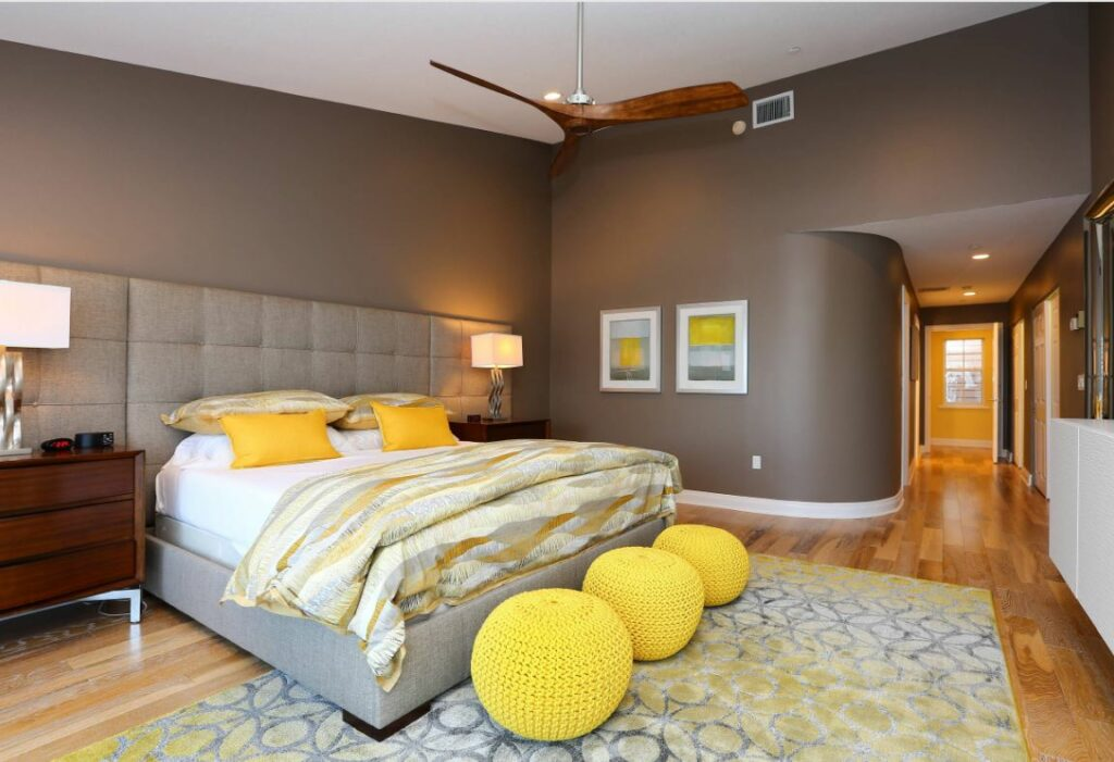 yellow and gray bedroom with three crocheted poufs