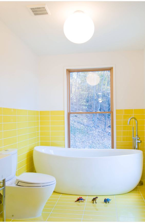 yellow tile standing tub window and dinosaurs in bathroom