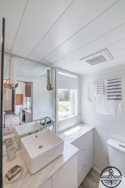 The bathroom has a small window as well just to the side of the vanity