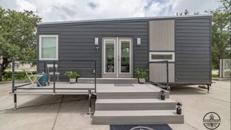 This tiny house has a deck at the front which basically extends the living area outside