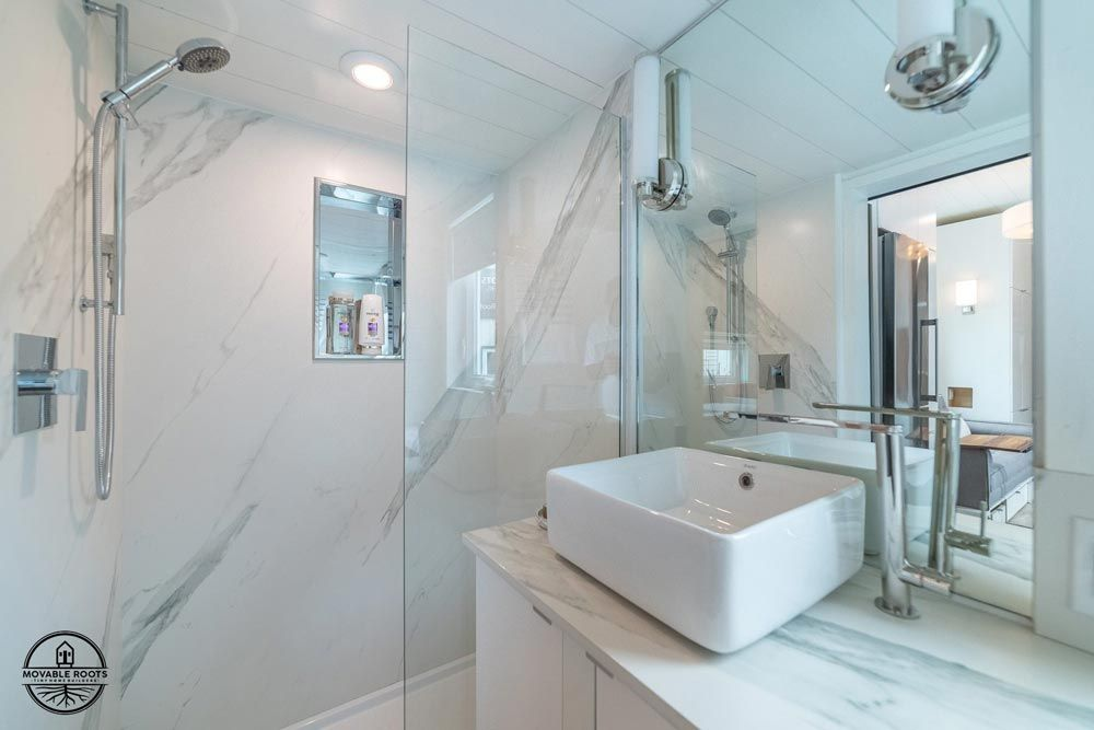 The bathroom is adjacent to the kitchen and has a walk-in shower with lovely marble tiles on the walls