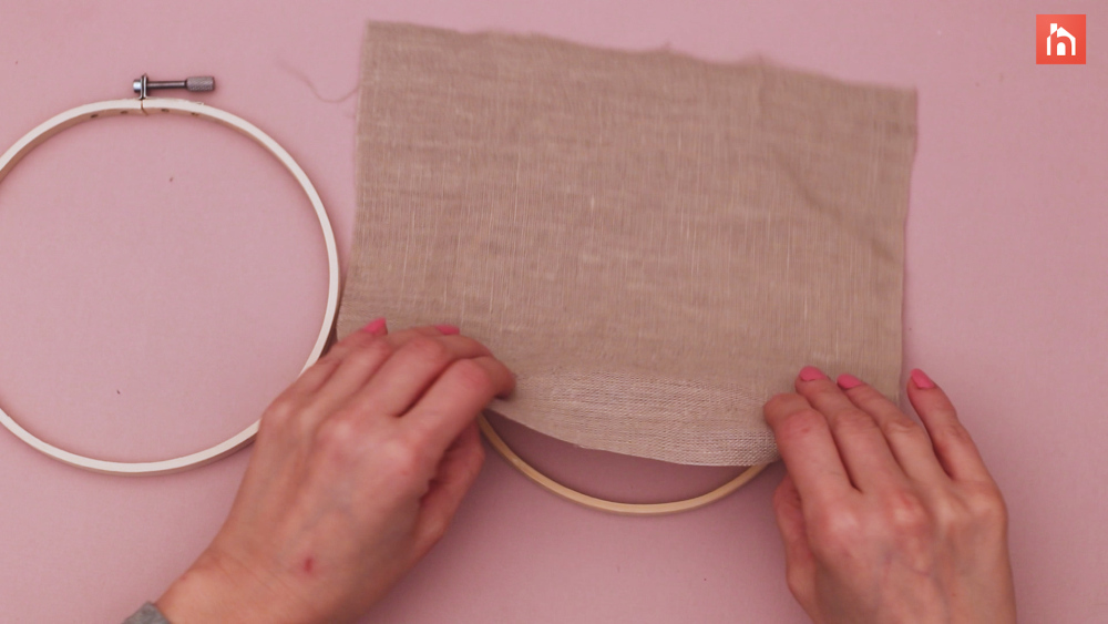 Secure the fabric between the two hoops