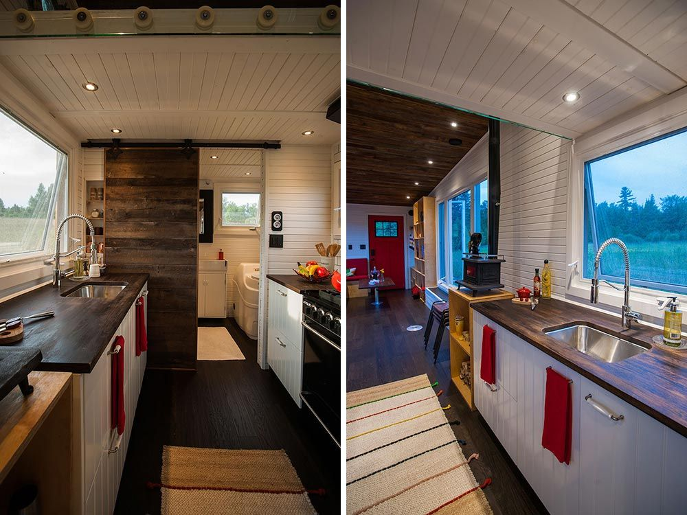 The bathroom is hidden behind a sliding barn door beyond the kitchen area