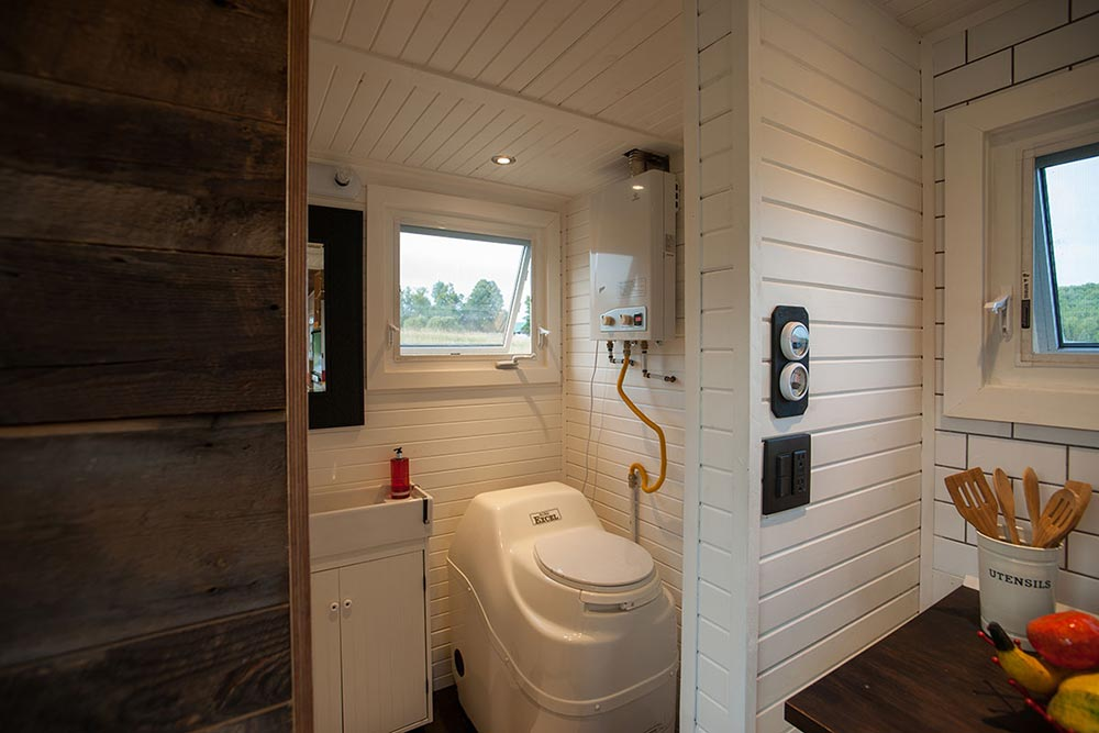The same horizontal pine wood walls were used to seamlessly connect the bathroom to the rest of the house