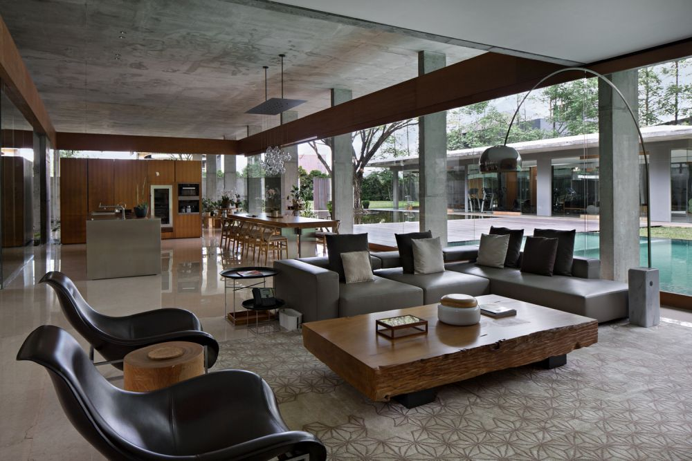 Inside, the living area is very big and has an open and airy layout with full-height windows