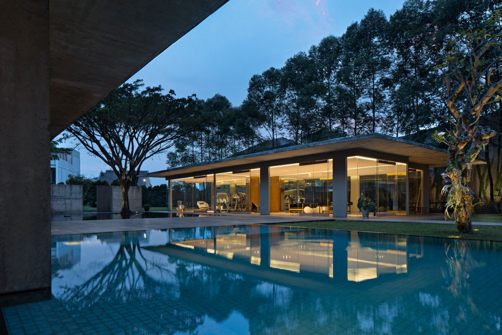 The poolside pavilion welcomes the outdoors in through its huge openings on all sides