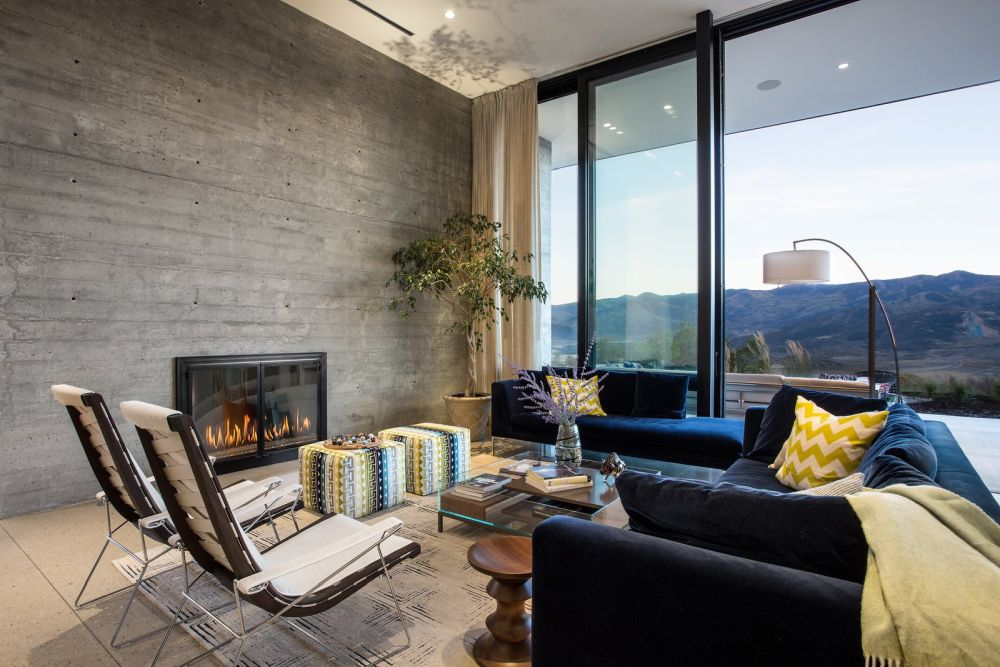 The full-height windows bring in the beautiful views and the fireplace gives this sitting area a very cozy feel