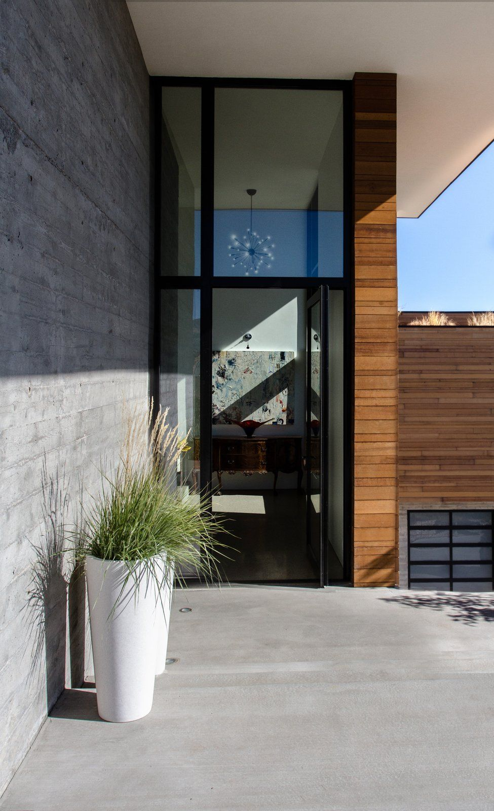 The combination of concrete, wood and glass is very fitting for a modern house such as this