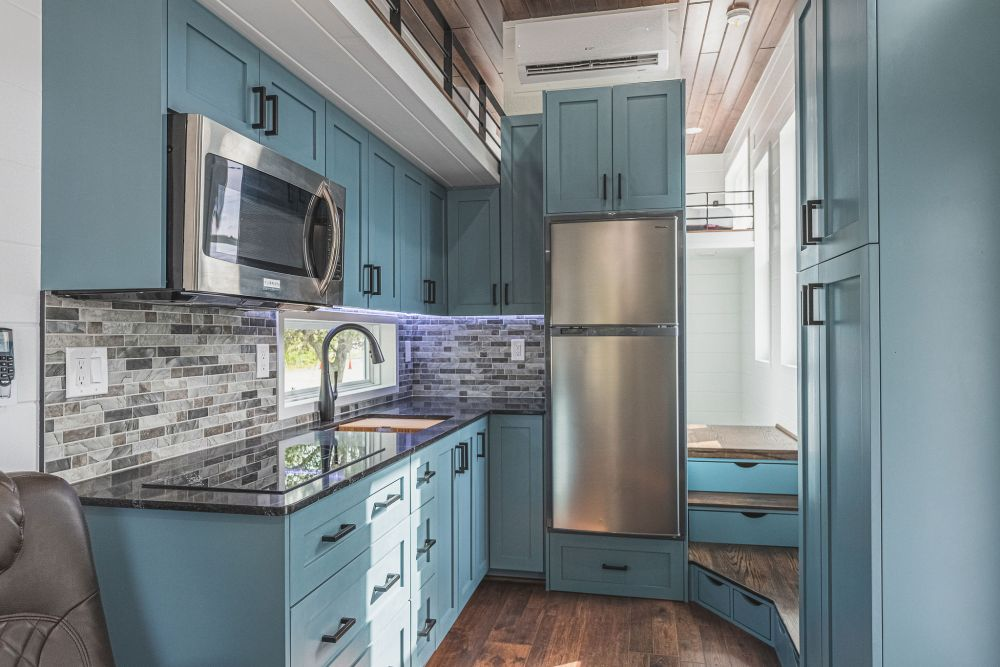 Inside there's a fairly spacious kitchen with a built-in refrigerator, microwave, sink, cooking station and lots of storage