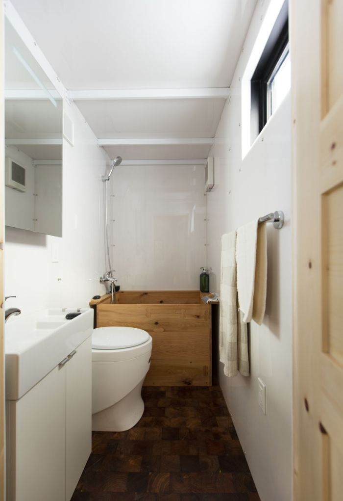 The bathroom has a vanity, a composting toilet and a soaking tub/ shower