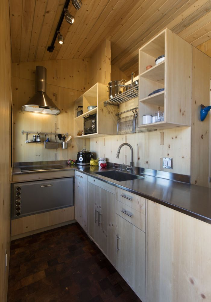 The kitchen has stainless steel countertops and plenty of storage above and below that