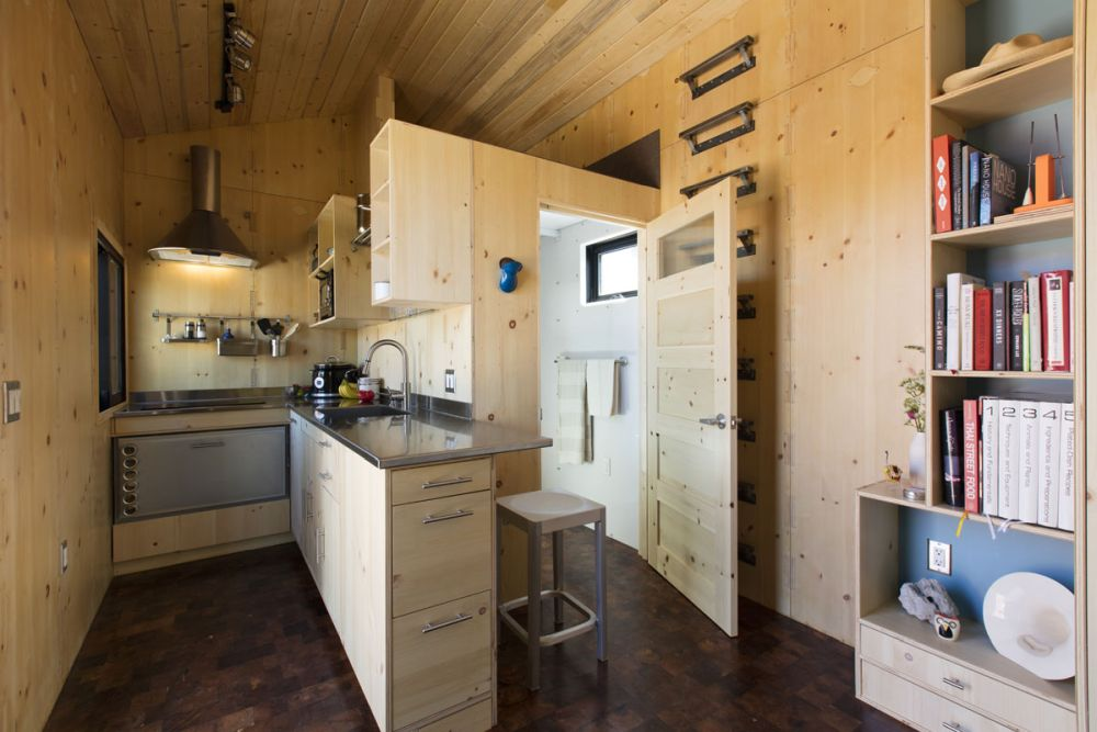 The kitchen is compact but well-equipped with an induction cooktop, a mini oven and a drawer refrigerator