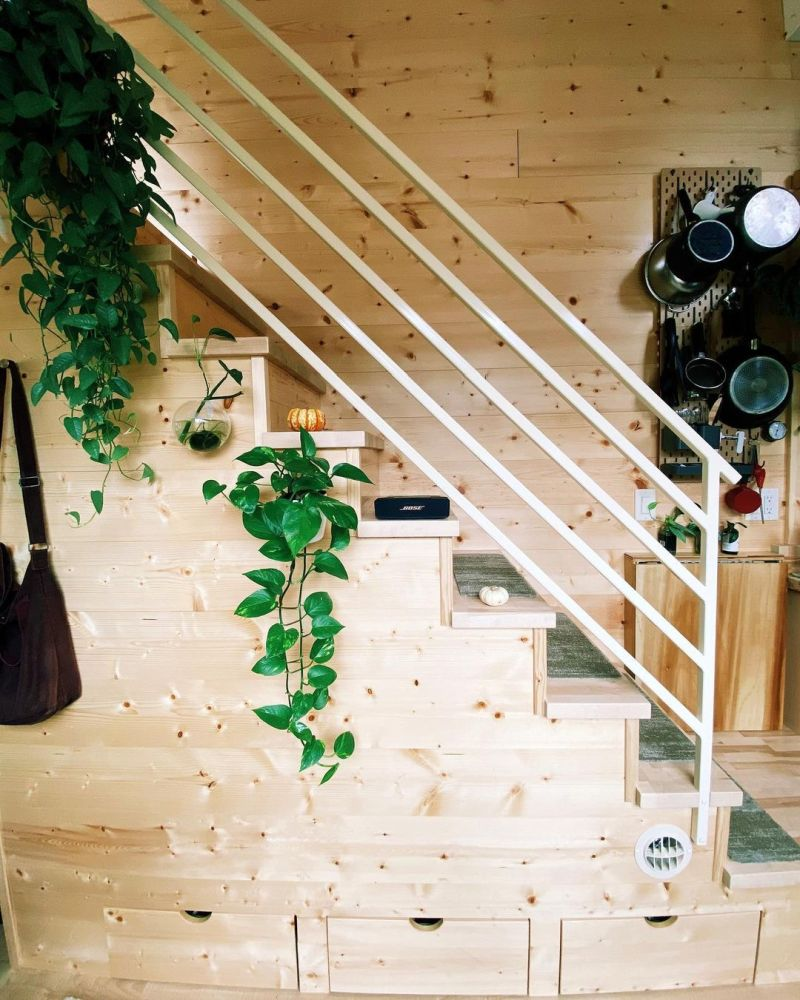 The staircase has built-in storage drawers and a coat rack to complement the entryway