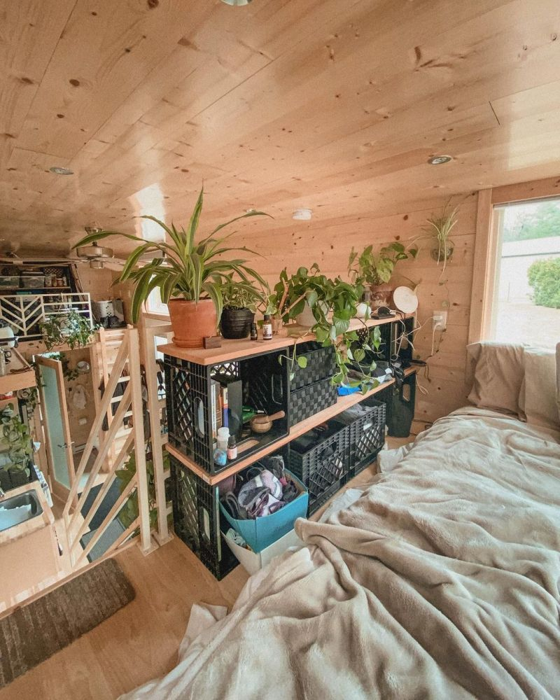 The sleeping area has a small closet made out of repurposed crates and wood planks