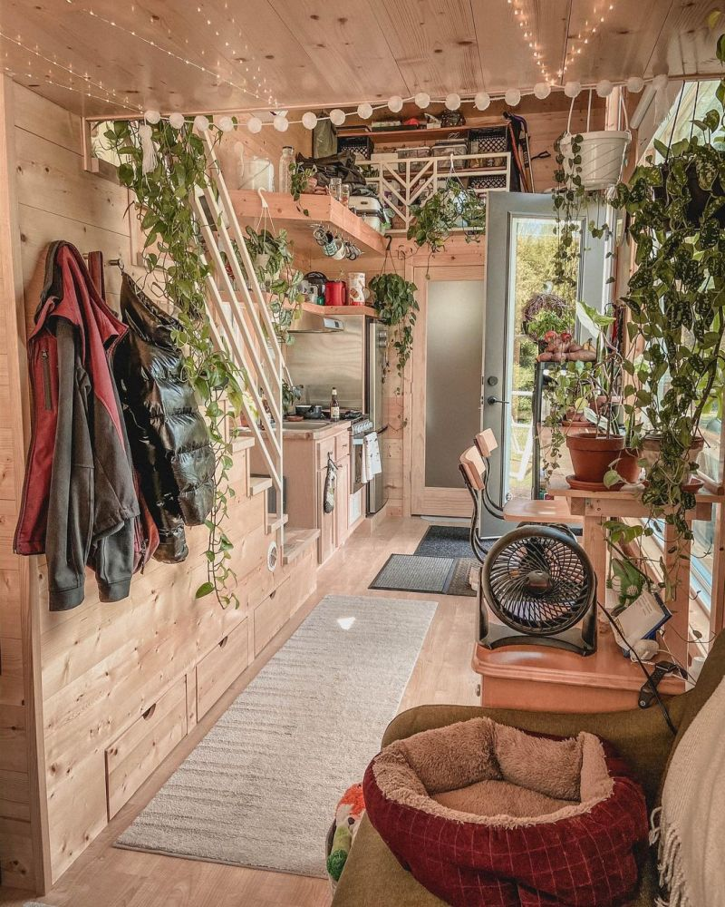 The interior is beautifully decorated with lots of hanging plants and string lights for a bohemian and cozy vibe