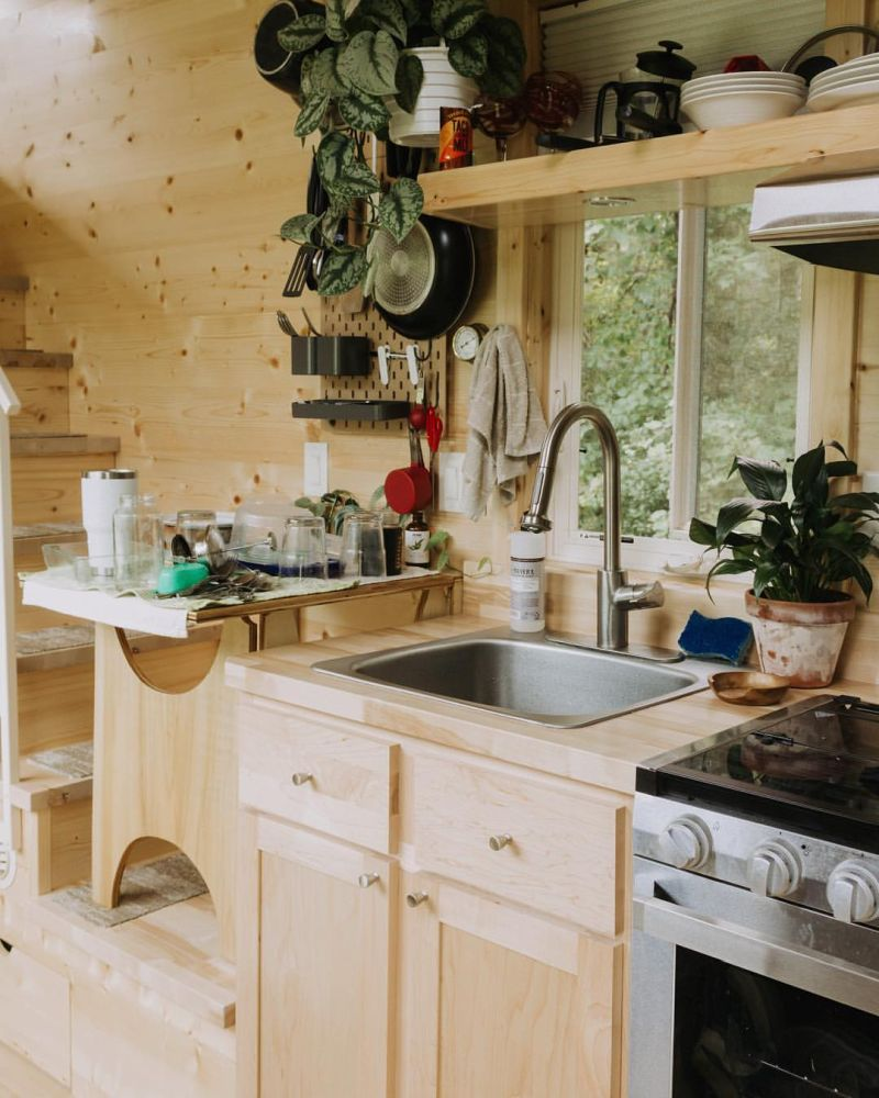 The kitchen is small but well-equipped, with storage shelves and a window in front of the sink