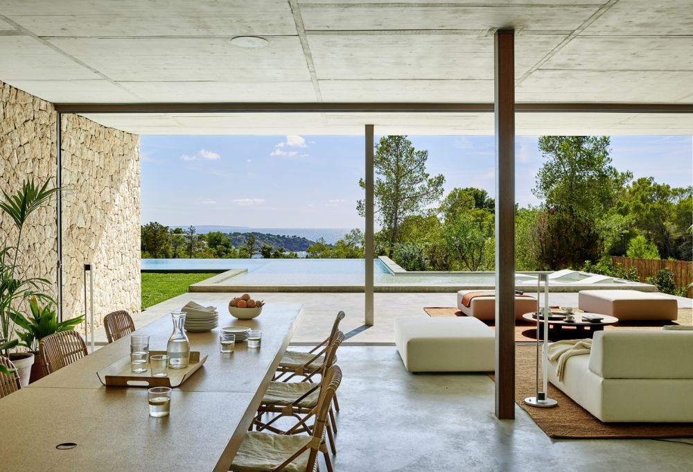 The expansive ground floor seamlessly transitions onto a patio and swimming pool area
