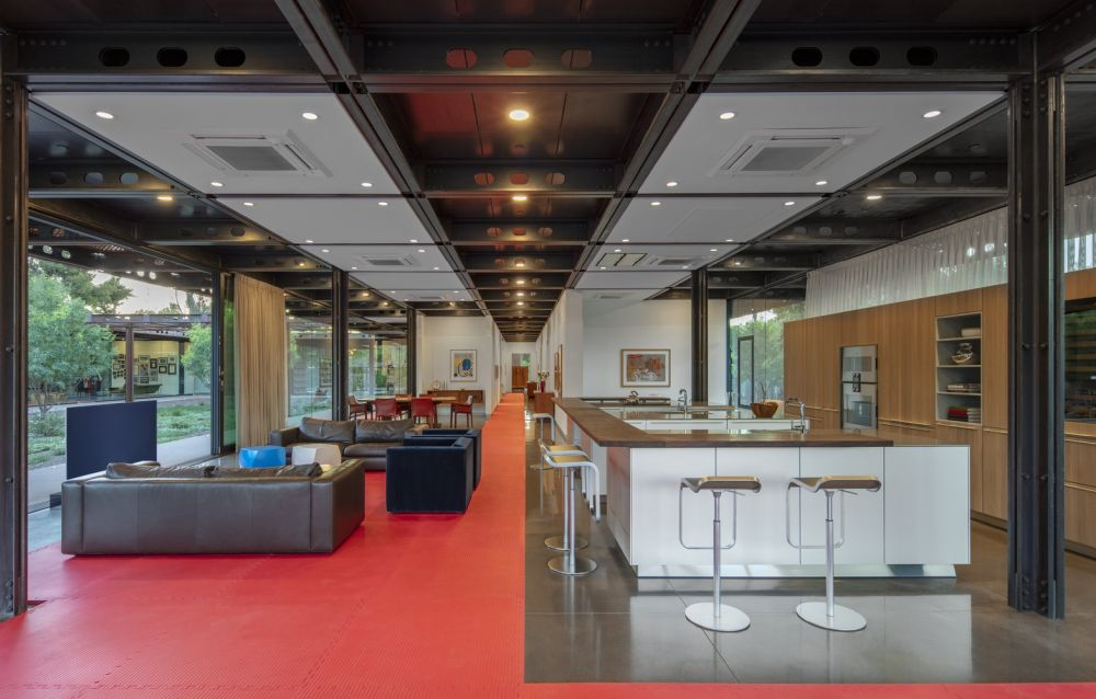 The large open floor plan is divided into modules and relies on visual separators such as area rugs and furniture