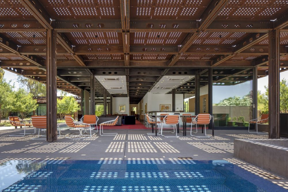 This is an expansive outdoor area sheltered under the perforated weathered steel roof
