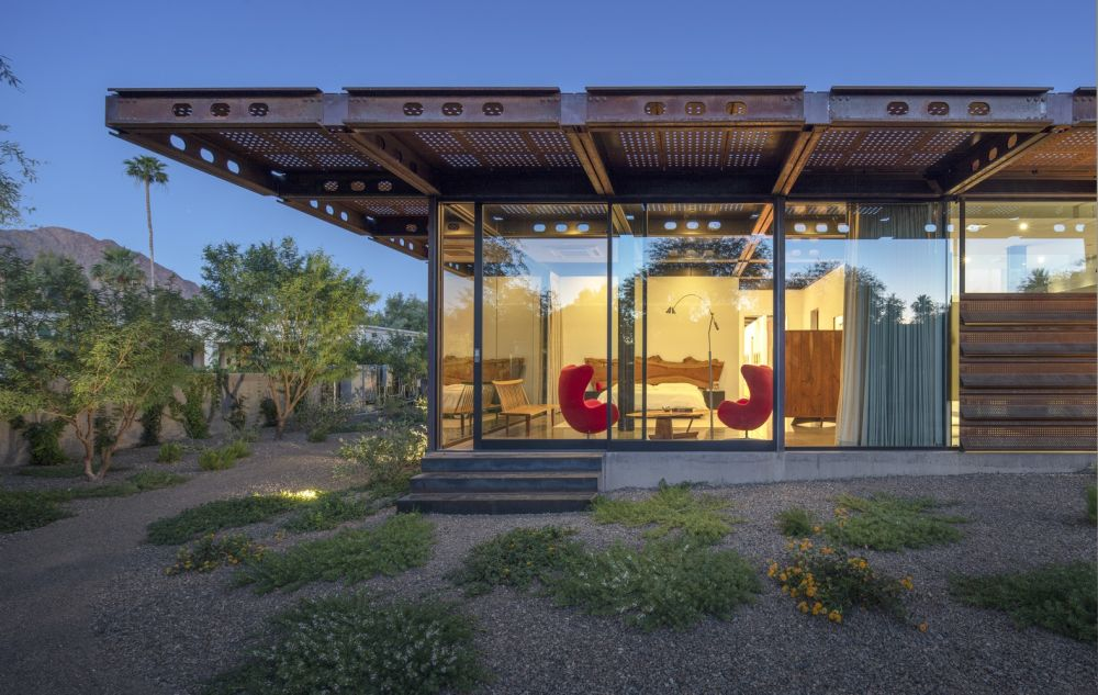 The house's Corten steel roof extends to create large cantilevers and numerous outdoor rooms