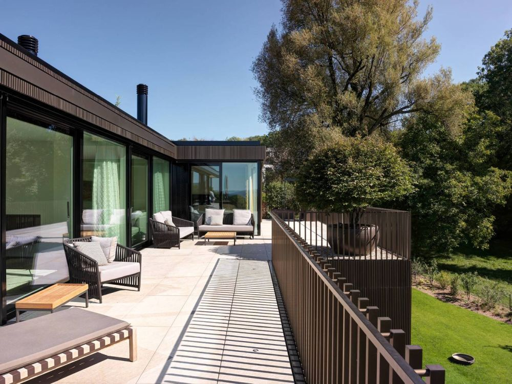 The metal facade also frames the open terraces on the upper floor areas, transitioning into stylish railings