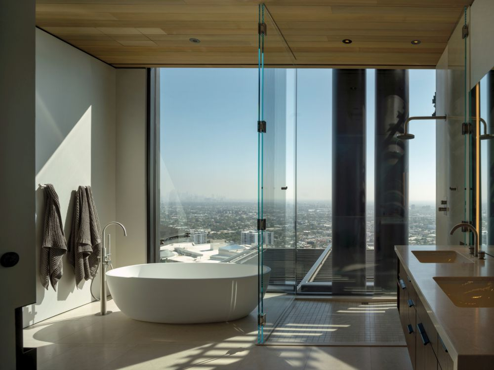 Full-height windows and glass walls turn the master bathroom into a relaxing luxury spa