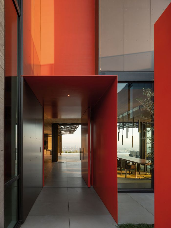The main entrance is marked by bright red walls which add a modern dynamic to the facade