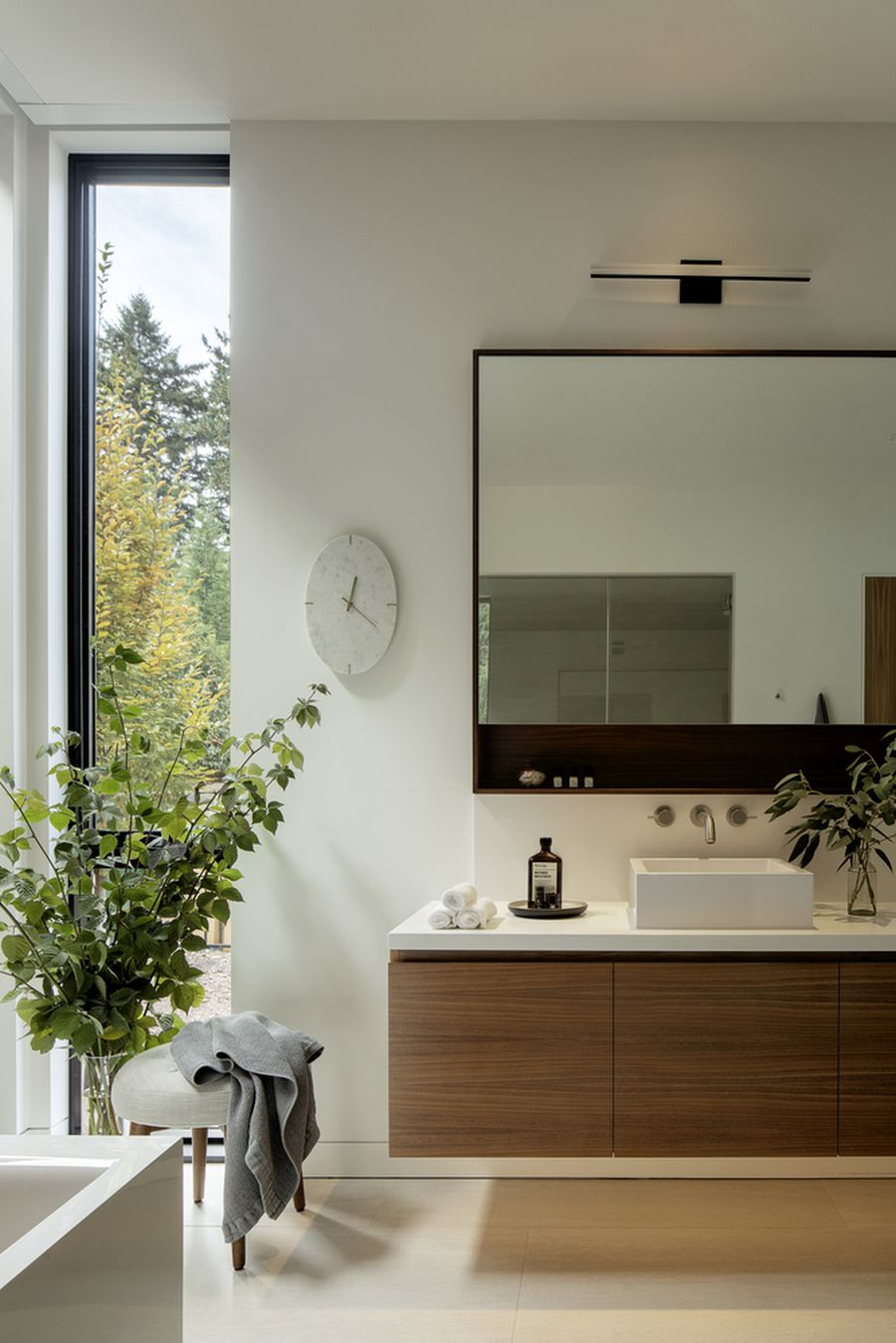 Tall vertical windows let light and lovely views into the master bathroom