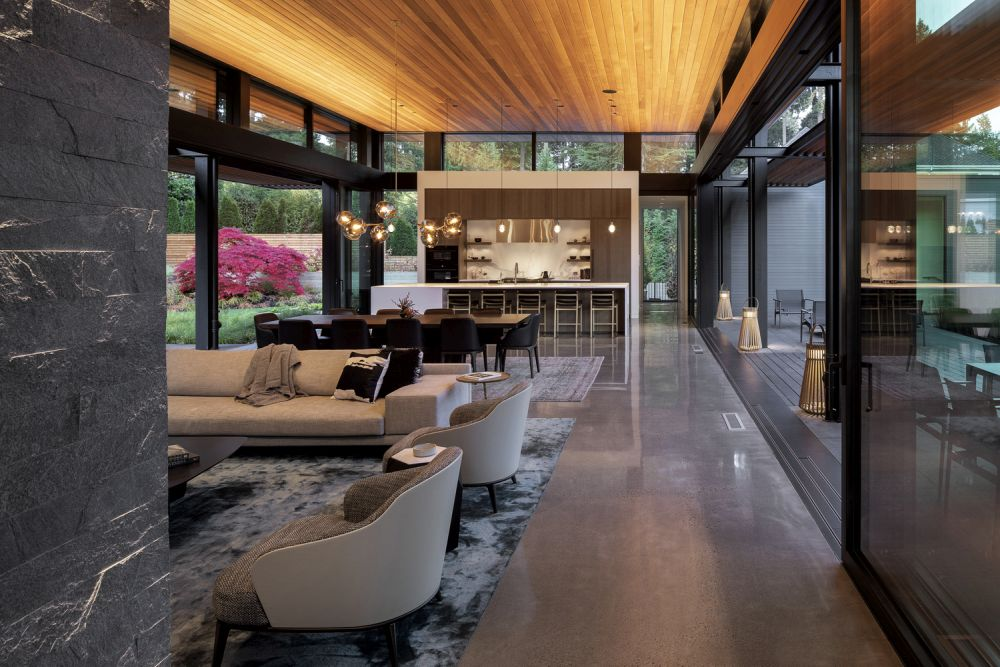 Big windows and sliding glass doors open up the living areas to the forest on both sides