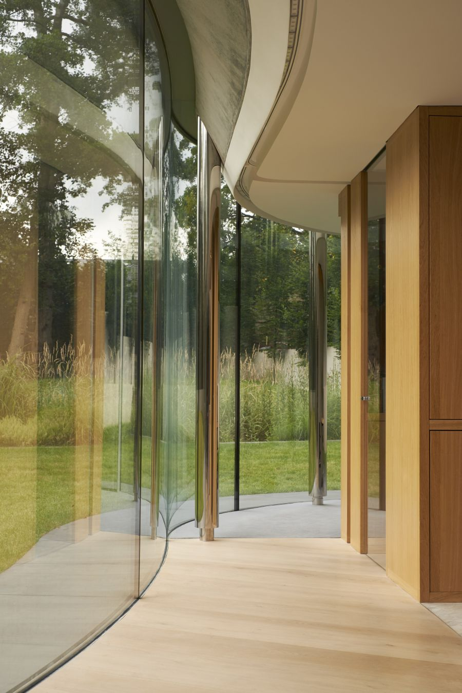 The curved glass facade creates a very immersive decor, allowing the landscape to envelop the house