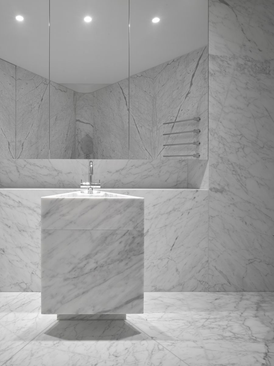 The minimalism of this bathroom puts all the attention on the beautiful white marble that covers the walls and the floor