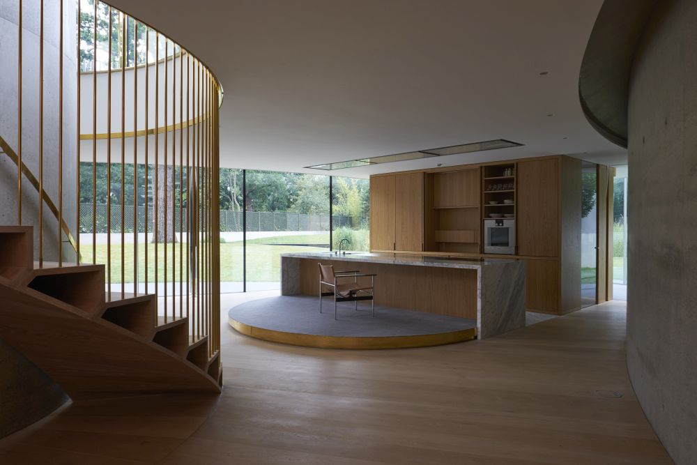 The kitchen island has an attached semi-circular raised platform which adds dynamism to the decor