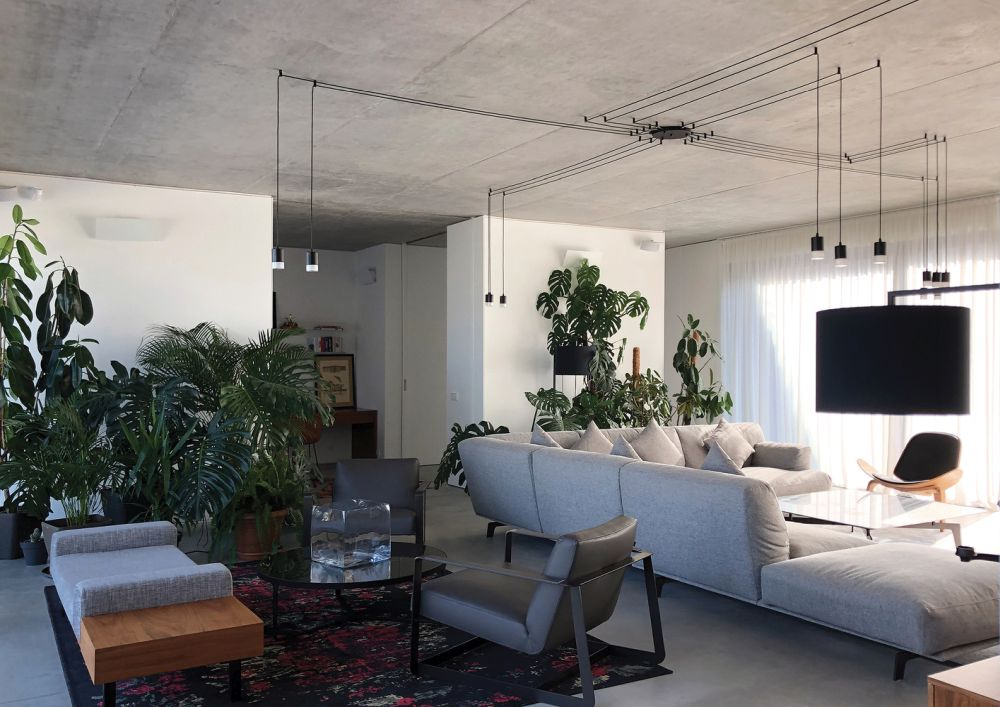 A stylish system of hanging lights illuminates the spacious living area in a really cool way